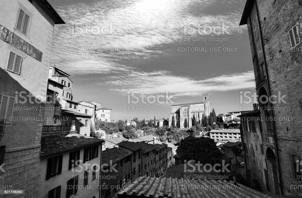 Black and white urban vista of traditional homes in Siena, Italy with Basilica san Domenico in the background stock photo