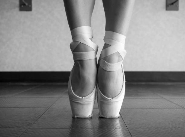 Black and white version of a close up of a ballet dancer's bare feet in pointe shoes stock photo