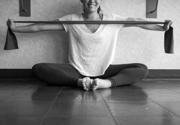 Black and white version of Smiling Young Active Female using a theraband exercise band to strengthen her arms muscles in the studio stock photo