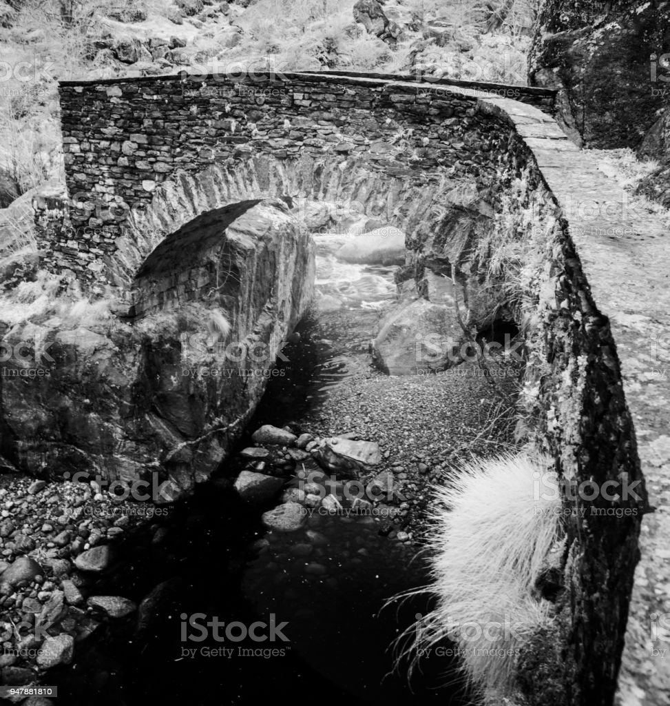 black and white view of beautiful old stone bridge crossing a small mountain stream in a wild and remote alpine valley stock photo