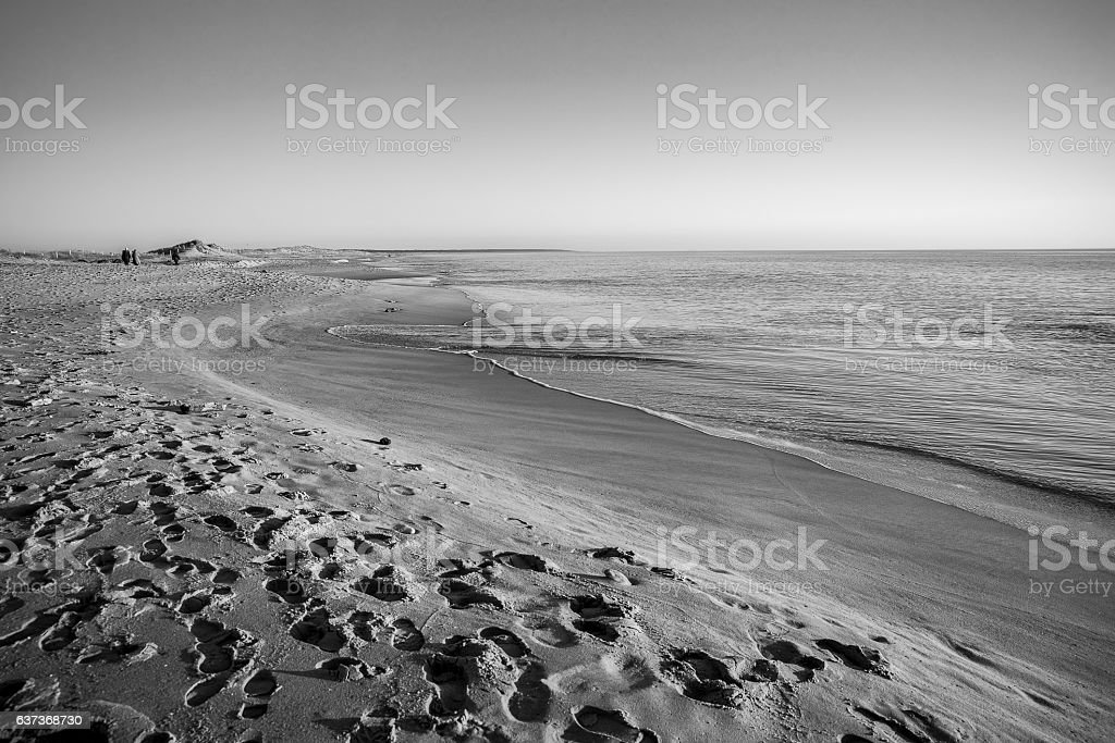 Black and white view of quiet beach and tranquil sea stock photo