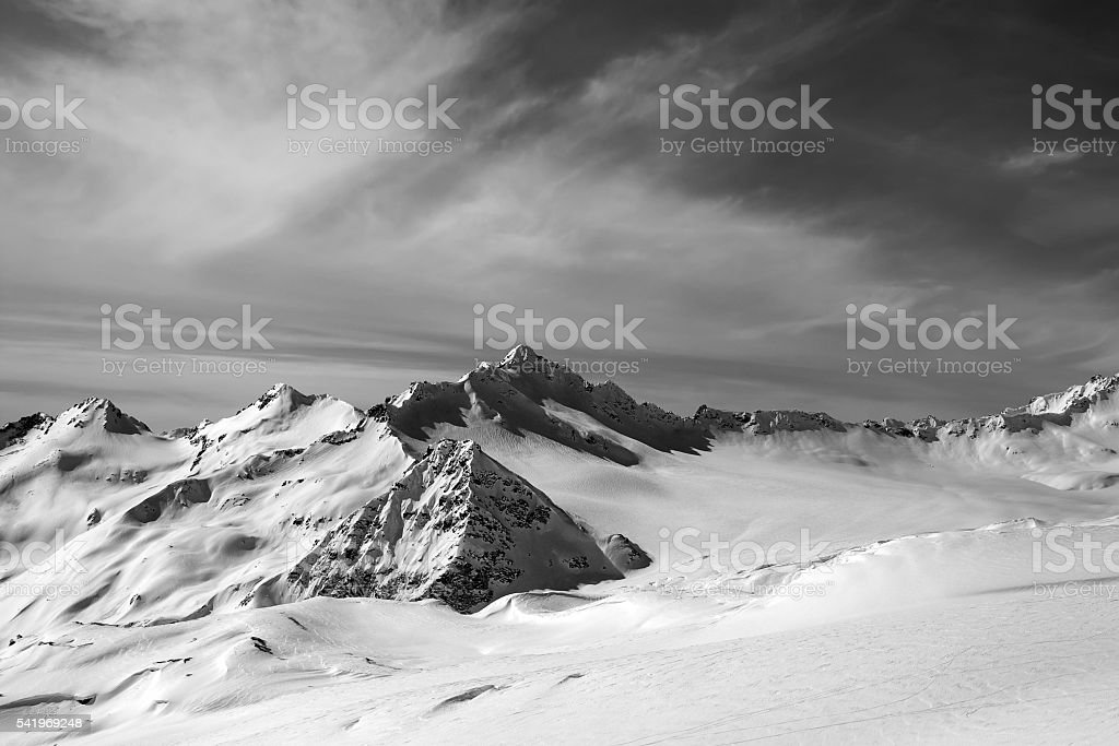 Black and white view on off-piste slope at sun evening stock photo