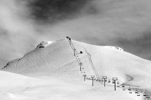 Black and white view on ski slope and chair-lift at sun winter morning