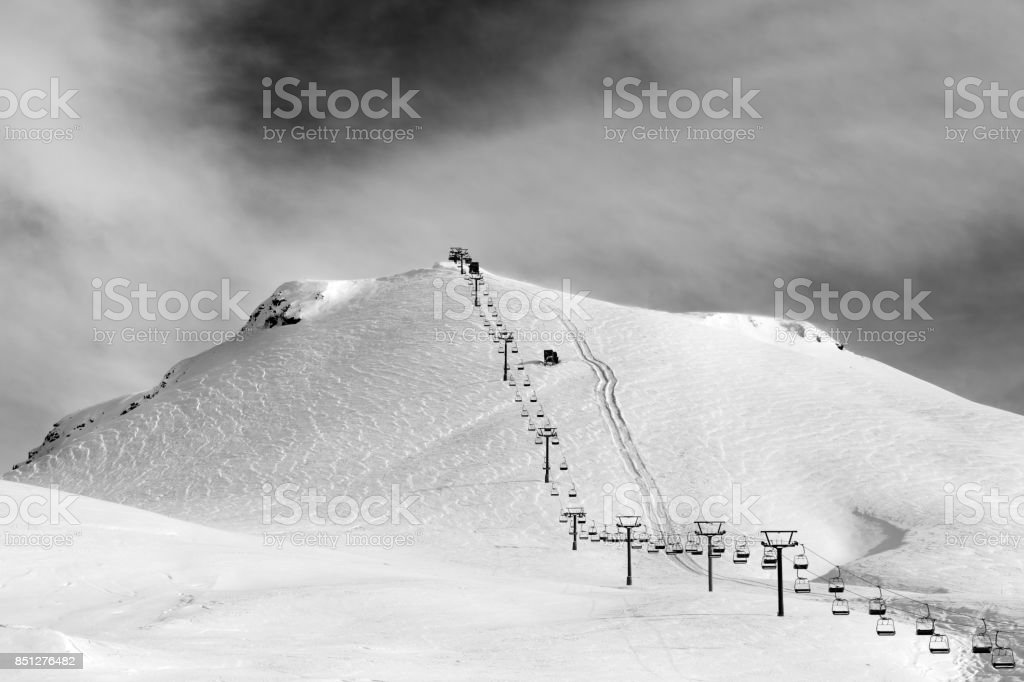 Black and white view on ski slope and chair-lift at sun winter morning stock photo