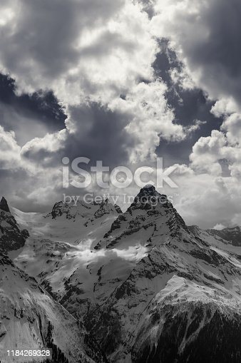 Black and white view on snowy evening mountains in sunlight clouds. Caucasus Mountains at winter, region Dombay, Mount Belalakaya.