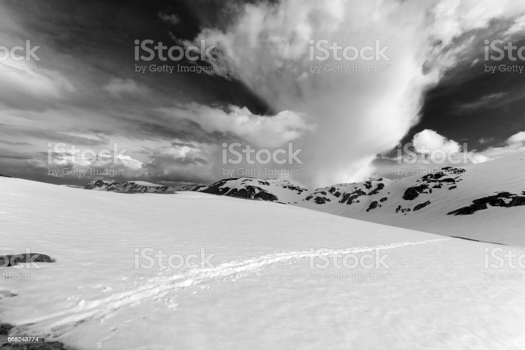 Black and white view on snowy mountains and sky with clouds foto stock royalty-free