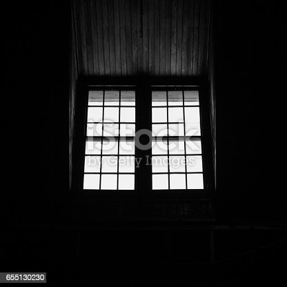 Light streams through windows at the Liberty State Park railroad and ferry terminal creating a beautiful silhouette. Image is black and white.
