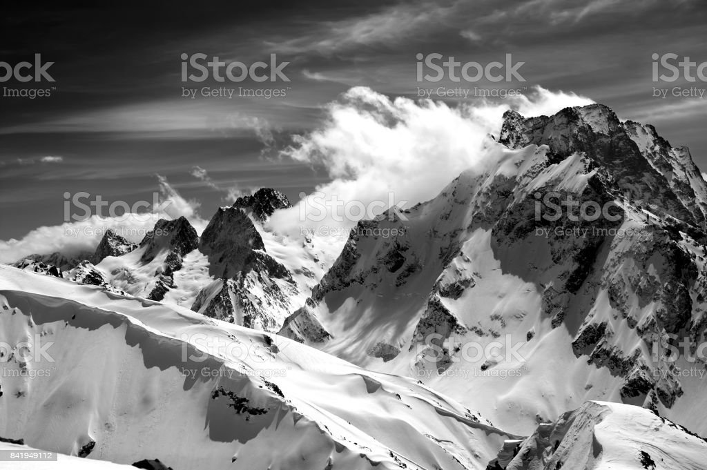 Black and white winter mountains with snow cornice and cloudy sky in nice sun day stock photo