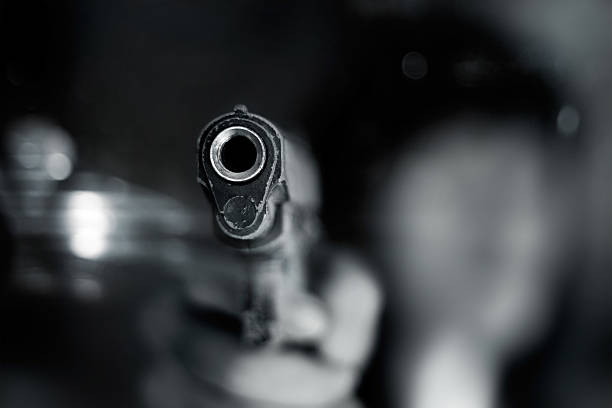 Black and white, woman pointing old gun to front Black and white, woman pointing a old gun to front with one Hand on dark background crime stock pictures, royalty-free photos & images