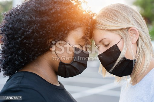 Black and white women together - African and caucasian women forhead to forhead and wearing protective face masks