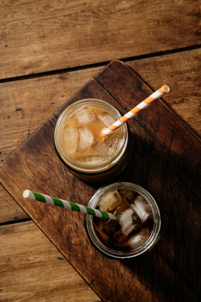 black and with mild iced cold brew coffee from above. - iced coffee stock pictures, royalty-free photos & images