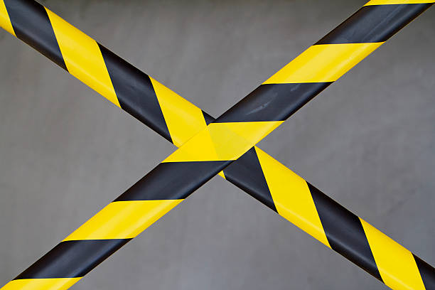 Black and Yellow Barrier Tape Black and Yellow Barrier Tape Blocking the Way affix stock pictures, royalty-free photos & images