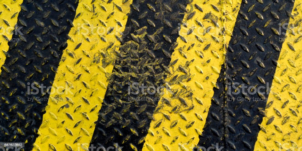 Black and yellow line paint on non-slip metal background stock photo