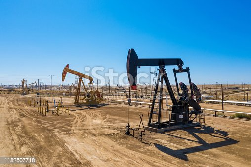 Black and yellow Oil pumps. Pumpjack. Oil industry equipment. Rig energy machine for petroleum crude. Daylight, morning, blue sky. USA