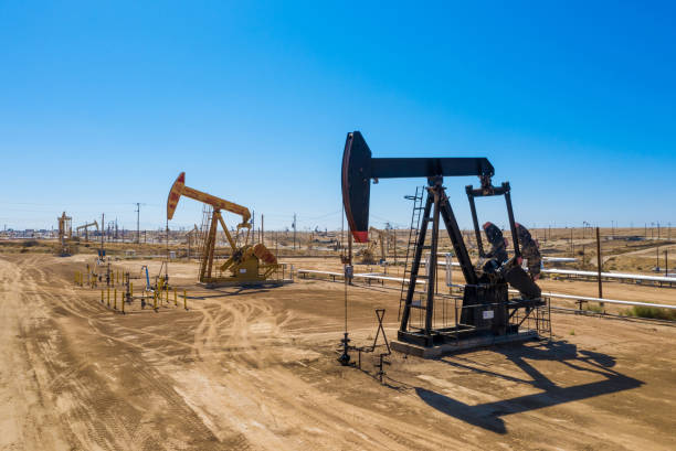 black and yellow oil pumps. pumpjack. oil industry equipment. rig energy machine for petroleum crude. daylight, morning, blue sky. usa - crude stock pictures, royalty-free photos & images
