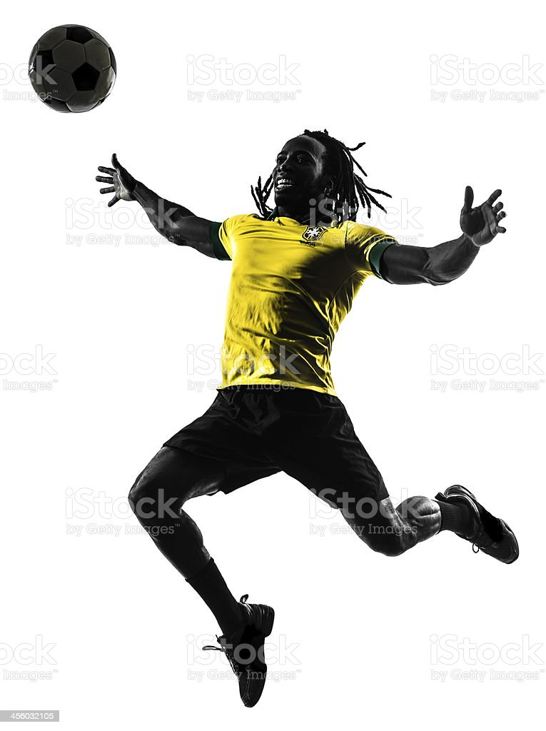 A black and yellow silhouette of a soccer player stock photo
