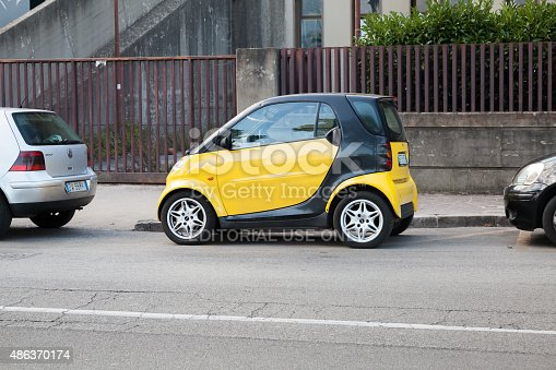 Gaeta, Italy - August 24, 2015: Black and yellow Smart car parked on urban roadside