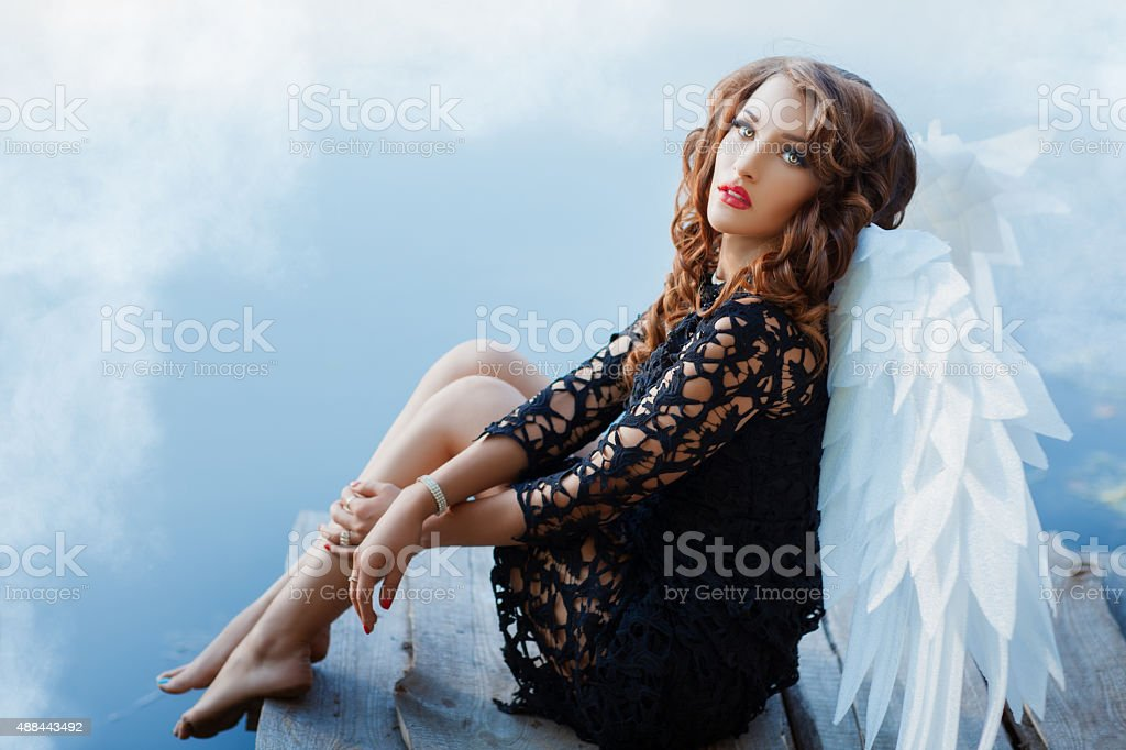 Black angel with white wings. stock photo