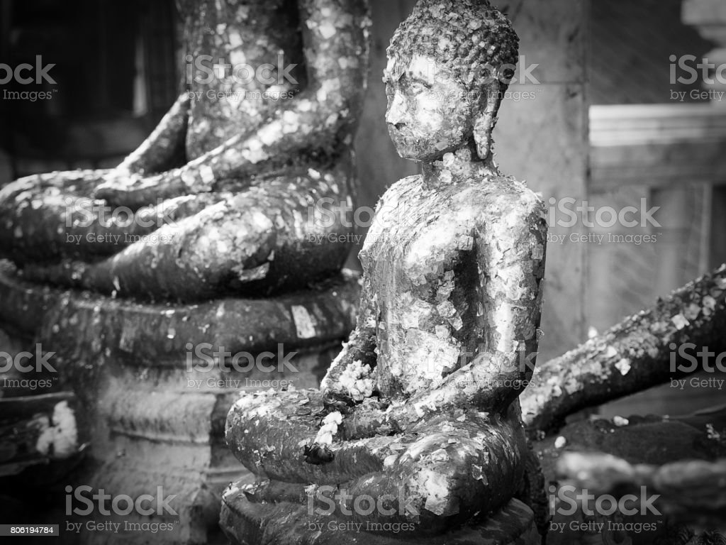 Black annd white Buddha statue with golden leaf. stock photo