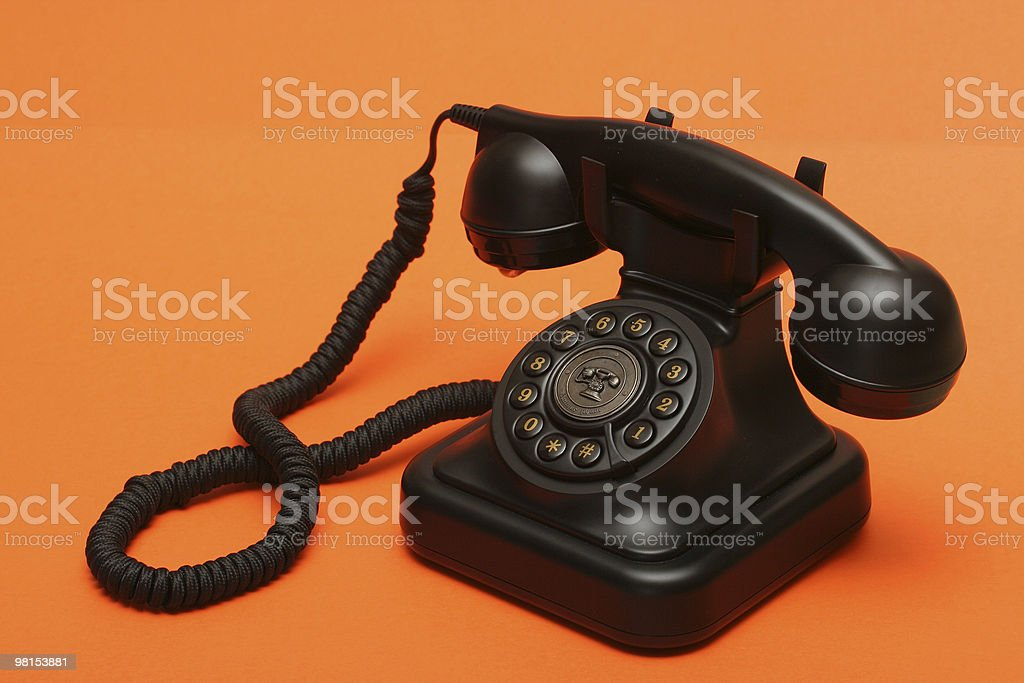A black antique phone on an orange background royalty-free stock photo