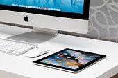 Black Apple Tablet iPad on white table near APPLE IMAC