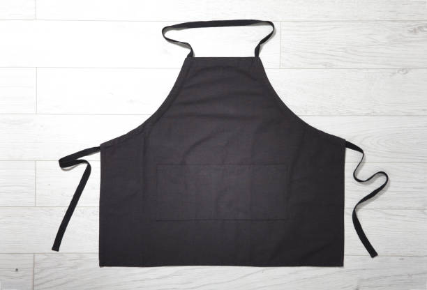 Black apron for kitchen top view on white wooden background. Black apron for kitchen top view on white wooden background. Mock up apron stock pictures, royalty-free photos & images