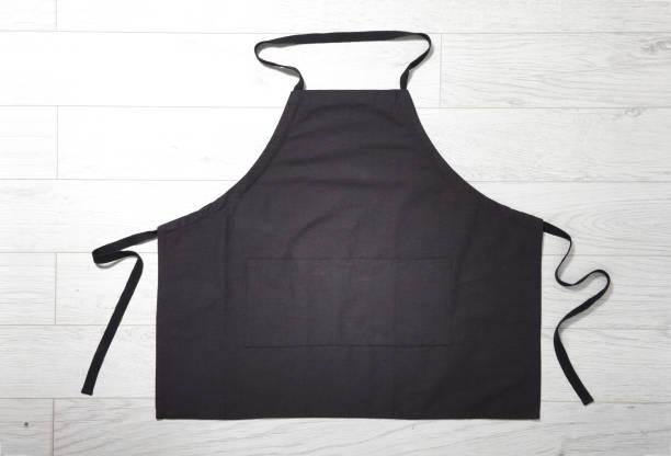 Delantal negro para la vista superior de la cocina sobre fondo de madera blanca. - foto de stock