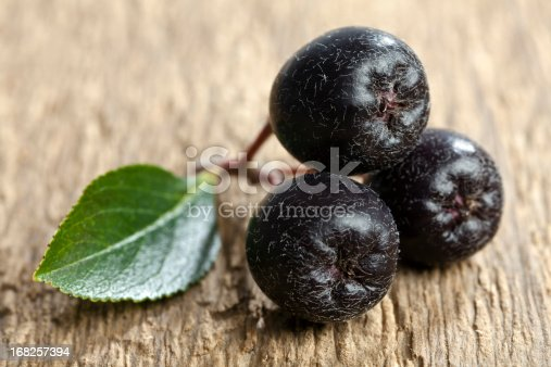 Black aronia with leaf isolated on wooden background.