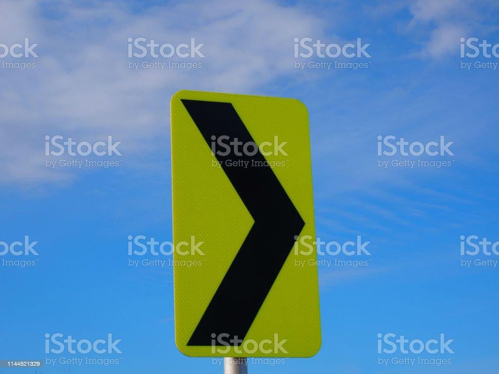 black arrow on yellow back traffic sign stock photo