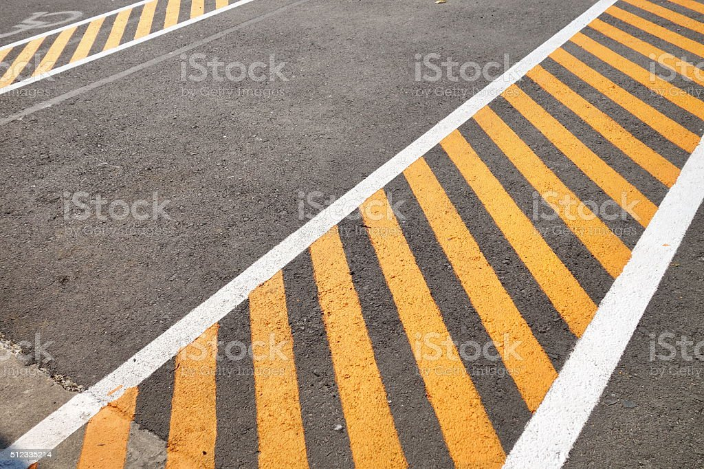 Black asphalt pavement painted with yellow stripes stock photo