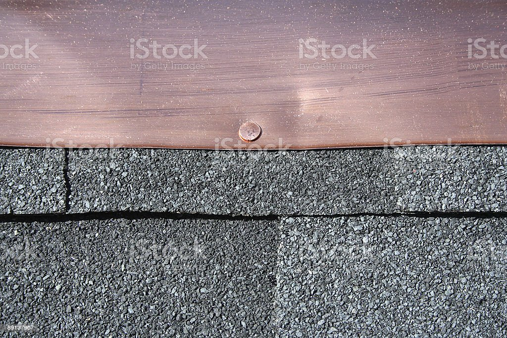 Black asphalt roofing shingles with copper flashing stock photo