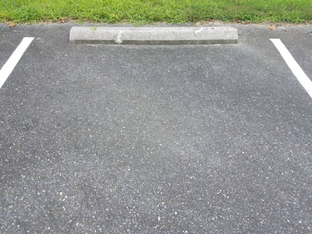 black asphalt with white lines and cement curb stock photo