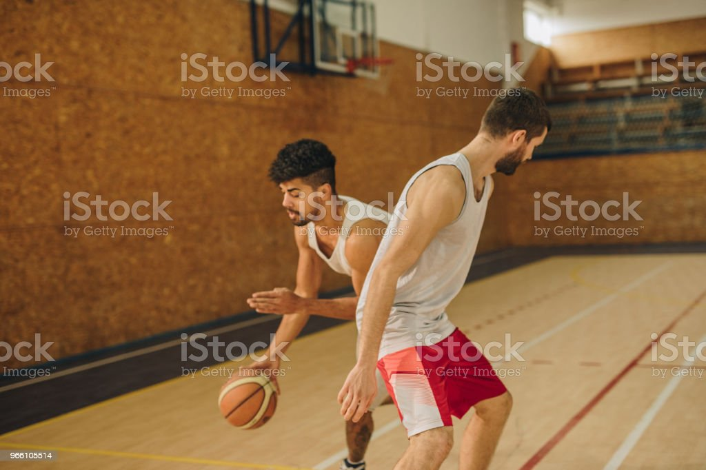 Black athlete dribbling his opponent on basketball match in sports hall. - Стоковые фото Активный образ жизни роялти-фри