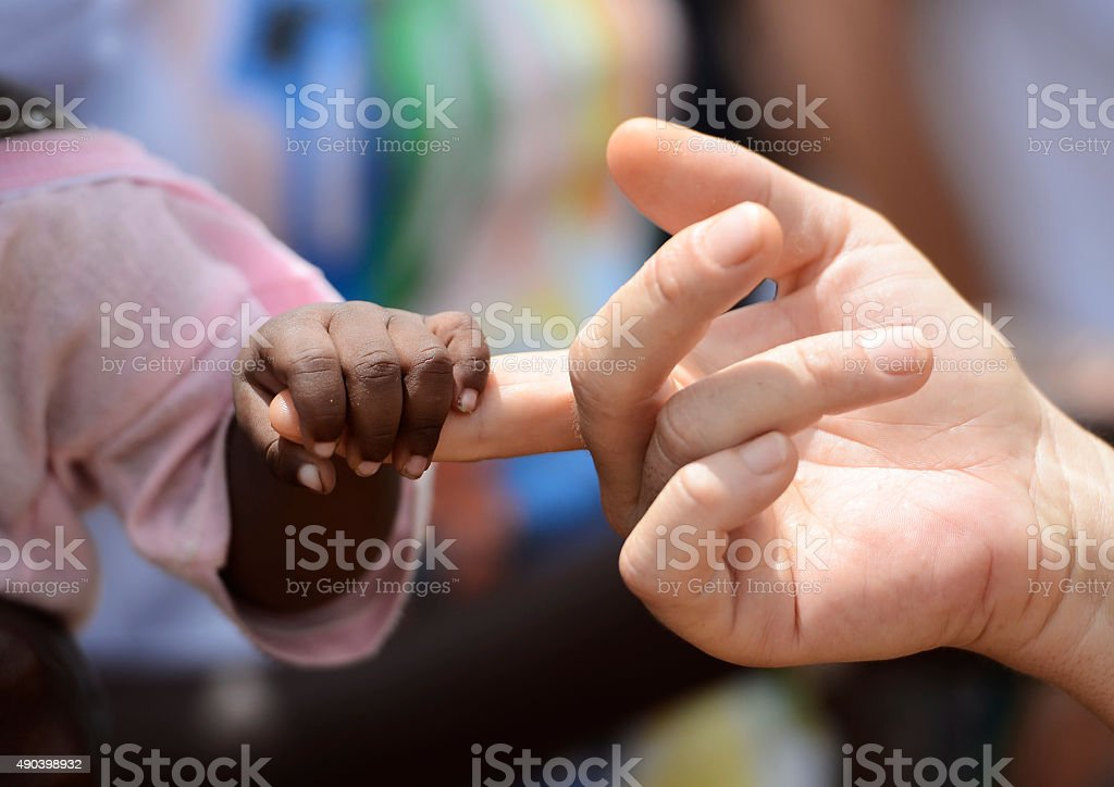 Black Baby and White Woman Holding Hands Fingers Africa stock photo