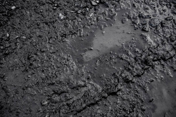 black background created from picture of tire trace on clay after raining surface. - mud stock photos and pictures