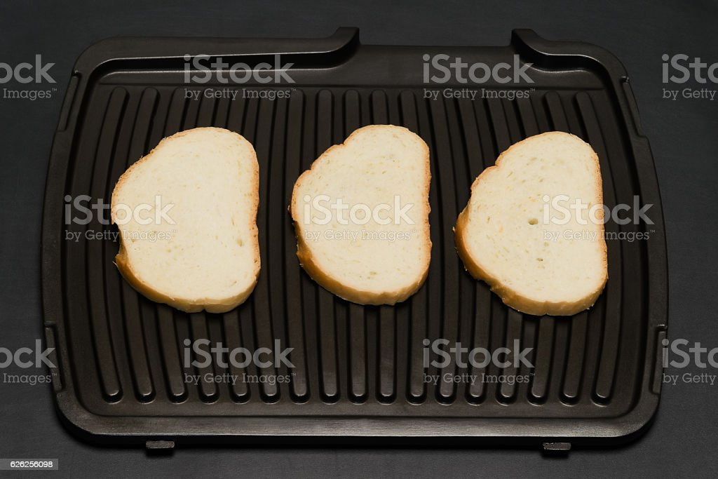 black background Three slices of bread on the grill stock photo