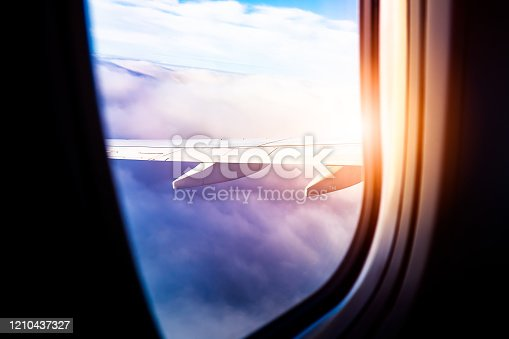 902818356 istock photo Black background with copy space with look of seat window frame of airplane flight see view of sunset clouds, airplane wing, ice mountains for luxury trip tourism travel transportation concept 1210437327