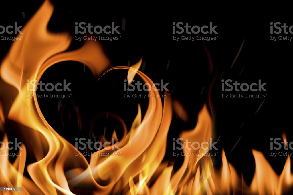 Black background with flames in the shape of a heart stock photo