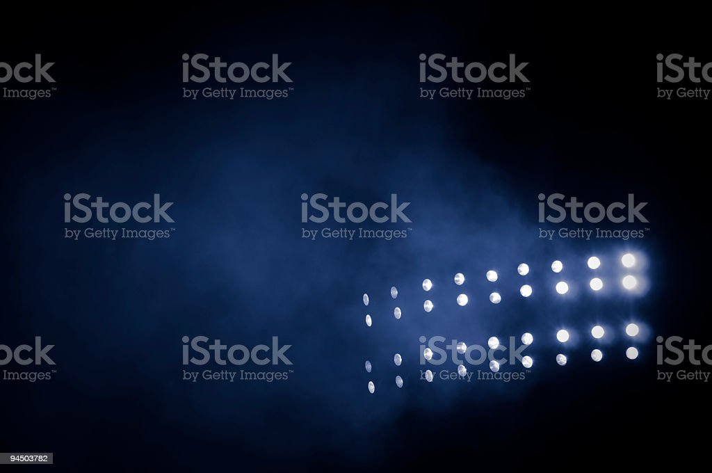 Black background with lit up stadium lights stock photo