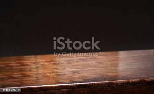 black background.Empty diagonal brown wooden table with blur black concrete wall backdrop,banner mockup template for display of product