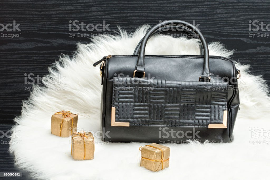 Black bag and gift box on white fur. Fashionable concept. Holiday shopping stock photo