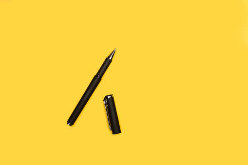 A black ball pen on a yellow background with copy space