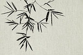 Black bamboo leaf and branch on fabric texture background
