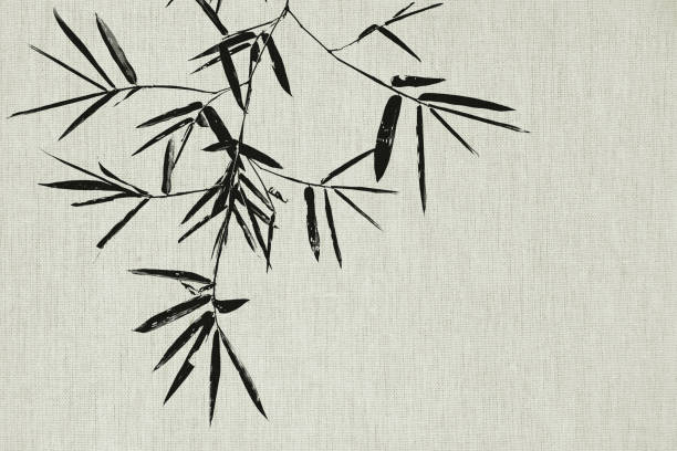 Black bamboo leaf and branch on fabric texture background stock photo