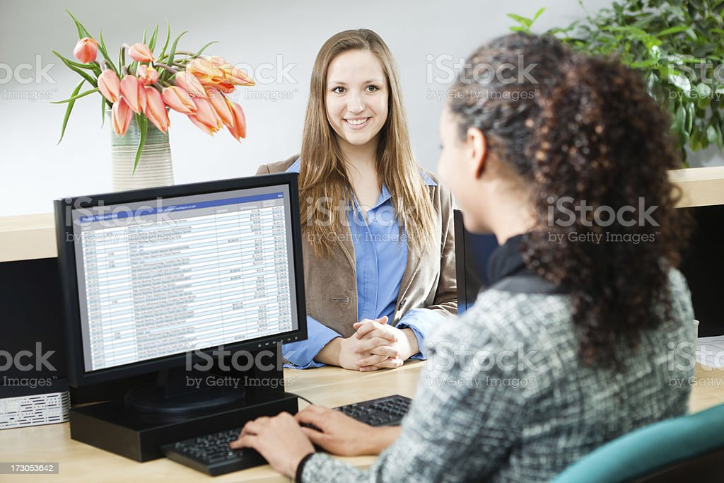 A Caucasian young woman approaching a bank counter to make a...