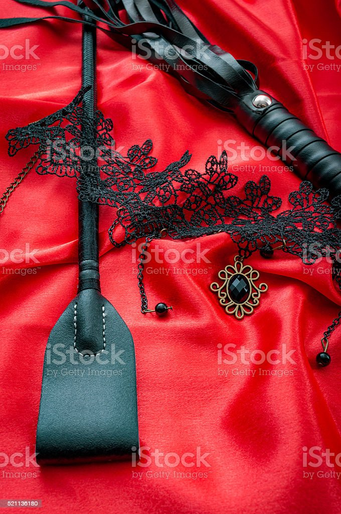 Black BDSM sex toys on red silk stock photo