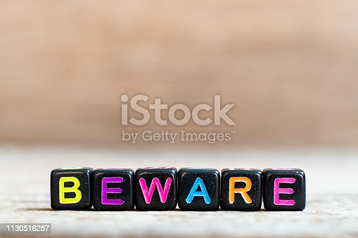 istock Black bead with color alphabet in word beware on wood background 1130516257