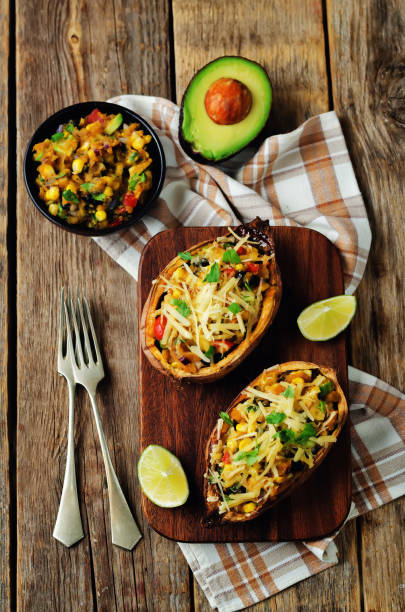 Black bean avocado corn stuffed sweet potatoes stock photo