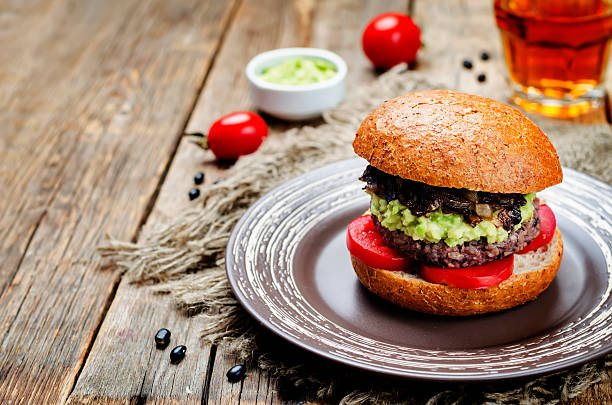 black bean burger with mashed avocado, caramelized onions and tomatoes stock photo
