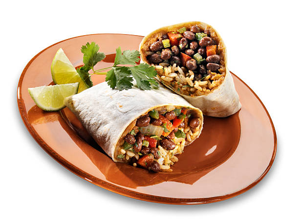 """Black Bean Burrito on white """"Single serving of a Black Bean burrito with black bean mixture, rice and refried bean rolled up and cut in half. Served with a wedge of lime. Drop shadow created in photoshop."""" burwellphotography stock pictures, royalty-free photos & images"""
